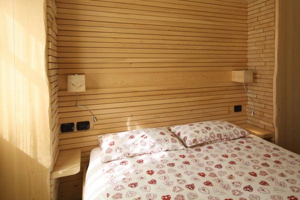 letto hotel testata parete legno